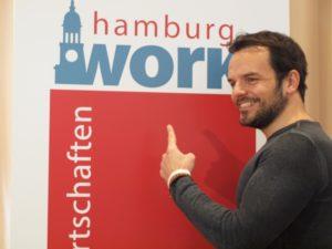 Steffen Henssler vor dem Aufsteller von hamburg work