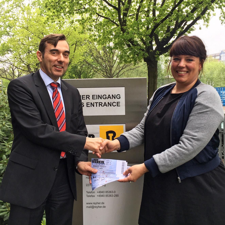 REYHER-Geschäftsführer Dr. Peter Bielert überreicht Pestalozzi-Betreuerin Yönna Hoge die Eintrittskarten (Foto: REYHER)